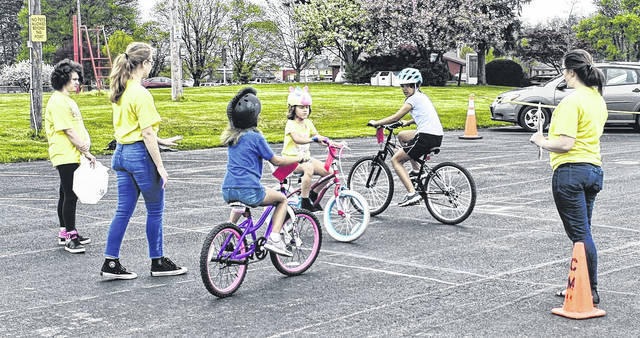 The Byrd sisters — Autumn, Avery and Abbi — practice stopping and yielding during the community bike rodeo at Denver Williams Park on Saturday. The event was sponsored by Wilmington Kiwanis, Wilmington Bike Club and Wilmington Parks & Rec.