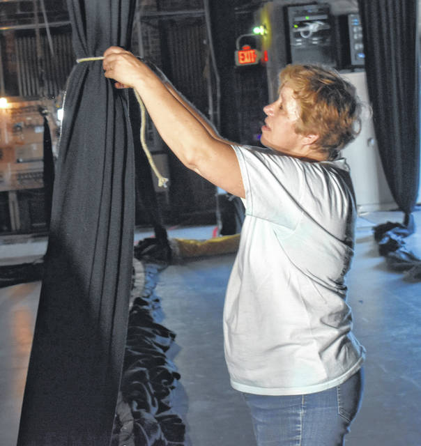 Murphy Theatre volunteer Diane Murphy helps get the stage curtains ready for storage as they update their stage rigging.