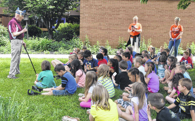 Paul Butler of the Forty and Eight Club and Clinton County Voiture 992 talks to the first-graders of Holmes Elementary about the significance and importance of the American flag on Tuesday. Each student got their own individual flag to take home. This is the 25th year the Legion has done this, according to Butler.