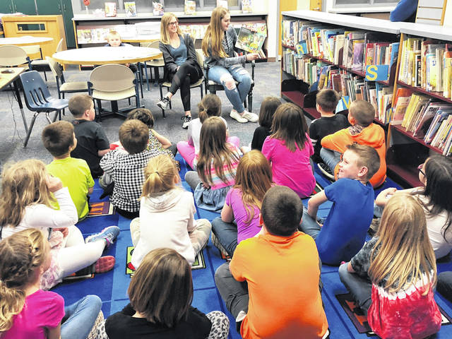 East Clinton High School recently observed National School Library Month with The Fable Guardians Book Club reading and donating books to the New Vienna and Sabina Elementary Schools' first-grade students. In the photo, Reese and Shelby read to Sabina first-grade children.