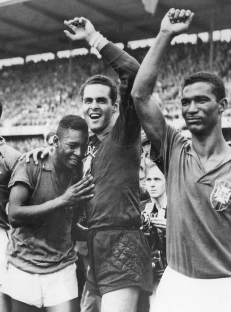 FILE - In this June 29, 1958 file photo Brazil's 17-year-old Pele, left, weeps on the shoulder of goalkeeper Gilmar Dos Santos Neves, after Brazil's 5-2 victory over Sweden in the World Cup final soccer match, in Stockholm, Sweden. Brazil's Didi is at right. Pele scored twice in that final. The 21st World Cup begins on Thursday, June 14, 2018, when host Russia takes on Saudi Arabia. (AP Photo/File)