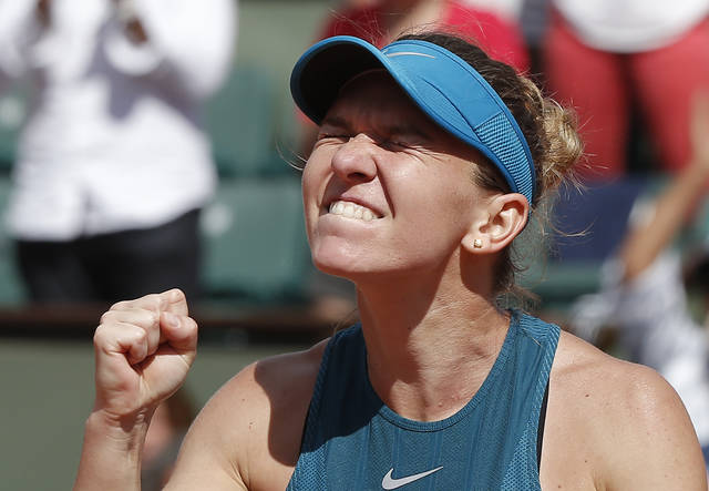 Romania's Simona Halep clenches her fist after defeating Spain's Garbine Muguruza during their semifinal match of the French Open tennis tournament at the Roland Garros stadium, Thursday, June 7, 2018 in Paris. Halep won 6-1, 6-4. (AP Photo/Michel Euler)