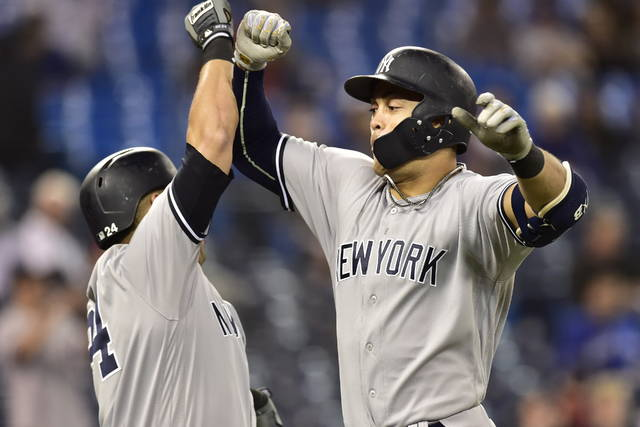 New York Yankees' Giancarlo Stanton, right, celebrates his home run against the Toronto Blue Jays during the 13th inning of a baseball game Wednesday, June 6, 2018, in Toronto. (Frank Gunn/The Canadian Press via AP)