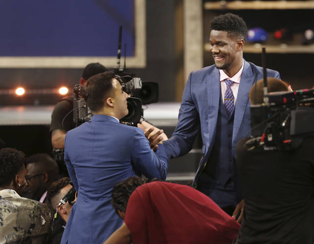 Arizona's Deandre Ayton, right, is congratulated by friends and family after he was picked first overall by the Phoenix Suns during the NBA basketball draft in New York, Thursday, June 21, 2018. (AP Photo/Kevin Hagen)