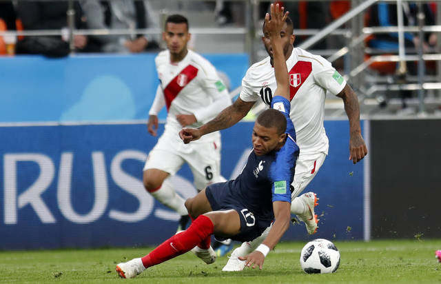 France's Kylian Mbappe is challenged by Peru's Jefferson Farfan, top, during the group C match between France and Peru at the 2018 soccer World Cup in the Yekaterinburg Arena in Yekaterinburg, Russia, Thursday, June 21, 2018. (AP Photo/Natacha Pisarenko)