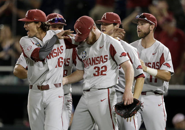Arkansas pitcher Blaine Knight, left, celebrates with Matt Cronin (32) and teammates after Arkansas beat Oregon State 4-1 in Game 1 of the NCAA College World Series baseball finals in Omaha, Neb., Tuesday, June 26, 2018. (AP Photo/Nati Harnik)