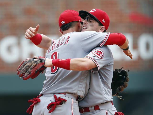 Cincinnati Reds second baseman Jose Peraza (9) embraces second baseman Scooter Gennett (3) after defeating the Atlanta Braves 6-5 in a baseball game Wednesday, June 27, 2018, in Atlanta. C(AP Photo/John Bazemore)