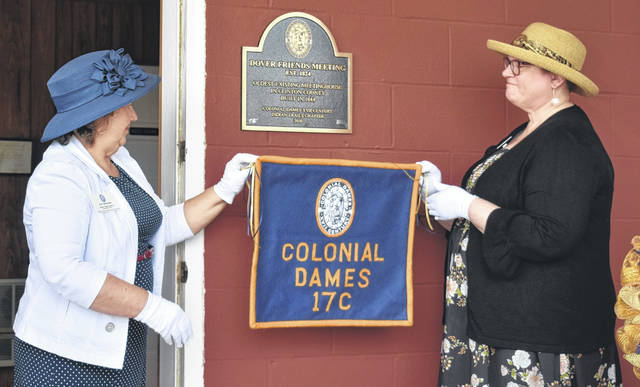 Members of Indian Trails and Colonial Dames Kay McIntire, left, and Kim Stackhouse unveils the historical plaque for the Dover Friends Meeting House on Sunday.
