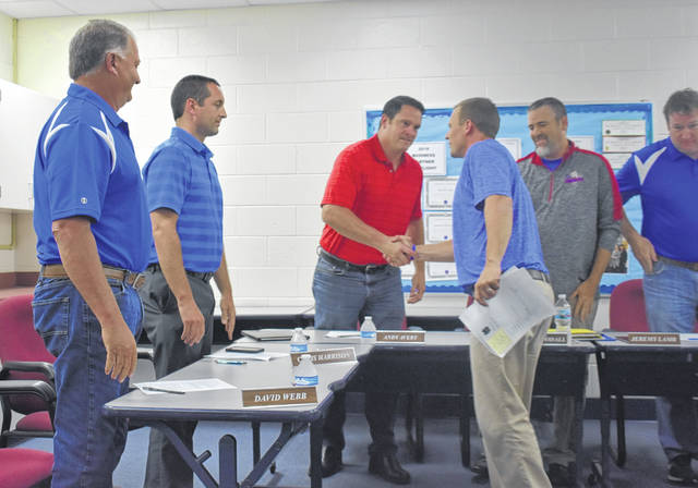Clinton-Massie Middle and High School Assistant Principal Aaron Seewer shakes hands with school board members after they approved him to be the new high school principal.