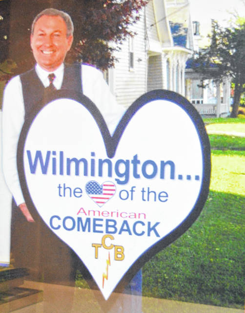 "This cardboard cutout of Butch Peelle holding a heart sign was an eye-catcher outside the Rombach Avenue offices of Peelle & Lundy Realtors, Inc. Wilmington sometimes was referred to as the poster child of the Great Recession; here we have Wilmington being offered as the heart of the American comeback from those hard economic times. The ""TCB"" at the bottom stands for Taking Care of Business."
