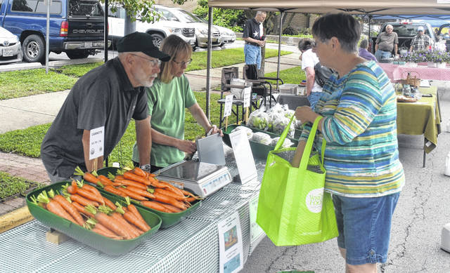 Mary Banner, right, buys some fresh produce from Henson Family Farm LLC at the Clinton County Summer Farmers' Market grand opening on Saturday.