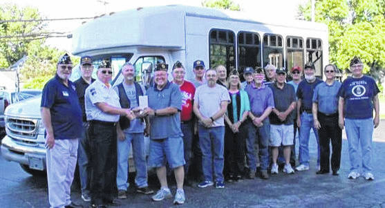 Wilmington American Legion Post 49 Honor Guard Commander Mike Sutton hands over the title for the bus to Blanchester Post 179 Commander Bruce Barricklow as Post 179 members look on.