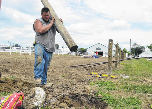 With the start of the 2018 Clinton County Fair just over three weeks away (July 7-14), Chad Seaman and Justin Lemmings of Seaman Construction are hard at work building new fences for the horse exercise ring and show ring on the fairgrounds. The durable fence is paid for through funds from the Ohio capital budget. Shown, Chad Seaman easily carries a fence post to its hole where the art and science of aligning straight fence posts takes over.