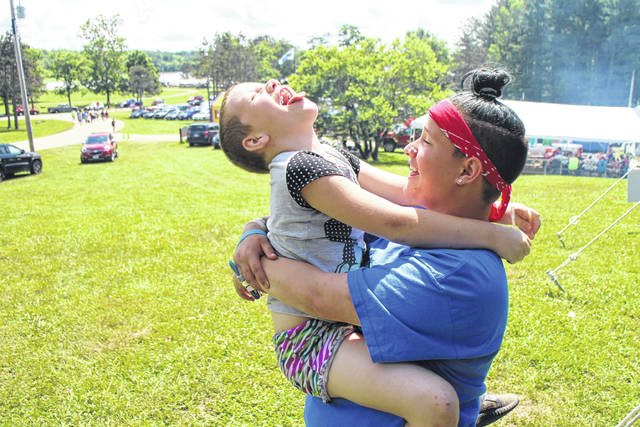 Elizabeth Gray, a camper at KAMP Dovetail, plays as she is held by volunteer Kendra Meiser on Friday.