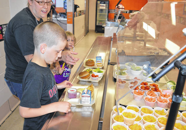 For the fifth year, Wilmington City Schools (WCS) is offering lunch free of charge this summer to all children 18 and younger in the community, regardless of household income. The meal service is weekdays 11 a.m. to 1 p.m. at the Wilmington Middle School cafeteria (except the Fourth of July). For adults, a meal is $3. For daily menus, please visit the WCS website and under the Departments tab click on Food Service. Getting lunches Thursday are, from front, Noah Logan, 8, mother Maria Logan, and Lily Logan, 6.