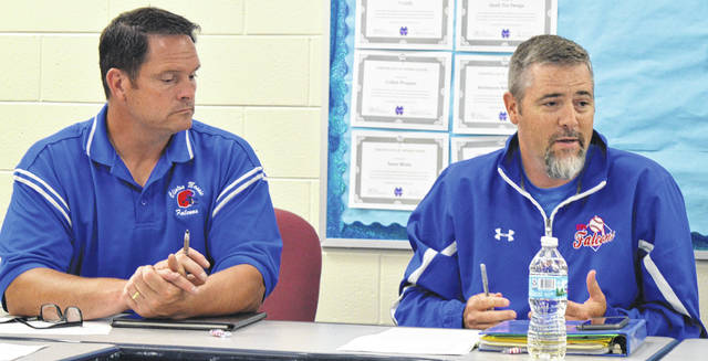 From left, Clinton-Massie school board members Andy Avery and Mike Goodall consider a proposed change to the open-enrollment policy, which later in the meeting was approved unanimously.