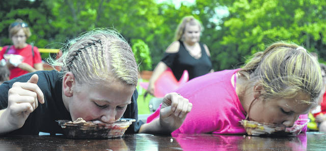 From left in the foreground, Clinton Countians Madison Robinson and Katelynne Robinson each devour a banana split without the use of their hands during Saturday's banana split eating contest for kids. The two relatives finished in a tie for first among children. Madison said her strategy was to eat from left to right. For more photos of the festival, see inside today's News Journal and online at wnewsj.com.