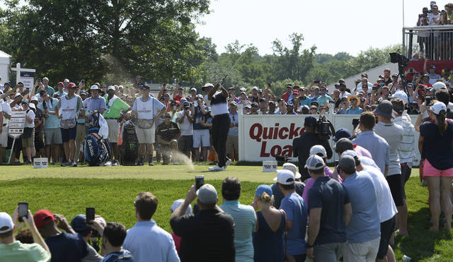 Tiger Woods, center, tees off on the 17th tee during the third round of the Quicken Loans National golf tournament, Saturday, June 30, 2018, in Potomac, Md. (AP Photo/Nick Wass)
