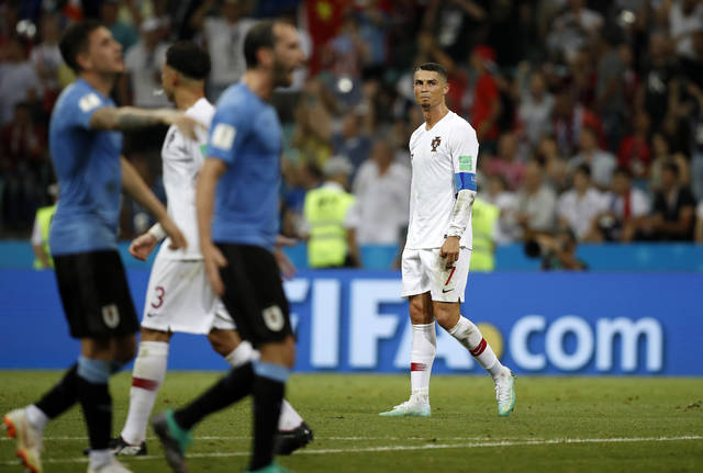 Portugal's Cristiano Ronaldo looks disappointed beside celebrating players of Uruguay after the round of 16 match between Uruguay and Portugal at the 2018 soccer World Cup at the Fisht Stadium in Sochi, Russia, Saturday, June 30, 2018. (AP Photo/Francisco Seco)