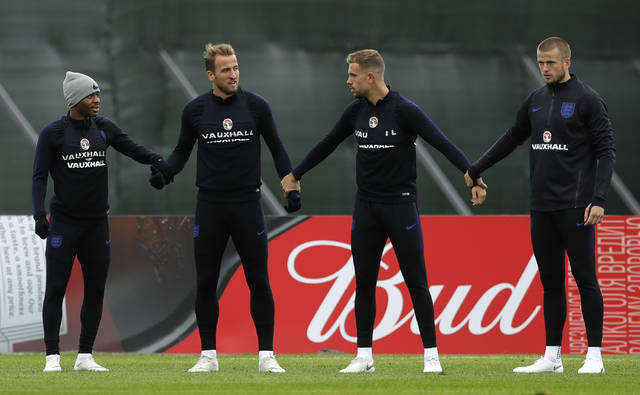 England's Raheem Sterling, left, with England's Harry Kane, England's Jordan Henderson, and England's Eric Dier hold hands as they play a game of tag during a training session for the England team at the 2018 soccer World Cup, in the Spartak Zelenogorsk ground, Zelenogorsk near St. Petersburg, Russia, Monday, July 2, 2018. (AP Photo/Alastair Grant)