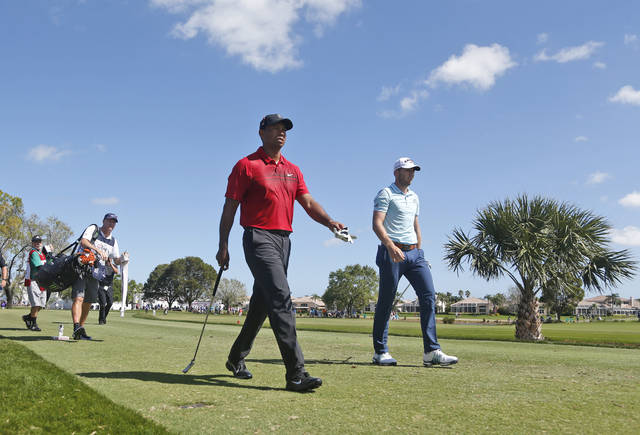 FILE - In this Feb. 25, 2018, file photo, Tiger Woods, center, and 21-year-old Sam Burns, right, walk off the tee on the fifth hole during the final round of the Honda Classic golf tournament, in Palm Beach Gardens, Fla. It was the first time the 42-year-old Woods had played with someone half his age. (AP Photo/Wilfredo Lee, File)