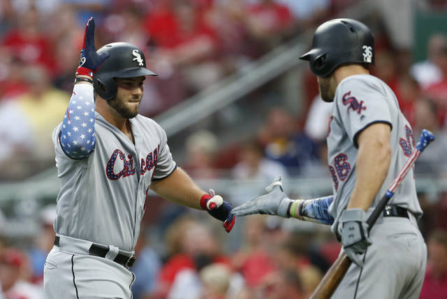 Chicago White Sox's Daniel Palka, left, is congratulated on a two-run home run off Cincinnati Reds starting pitcher Anthony DeSclafani by Kevan Smith, right, during the fourth inning of a baseball game, Tuesday, July 3, 2018, in Cincinnati. (AP Photo/Gary Landers)