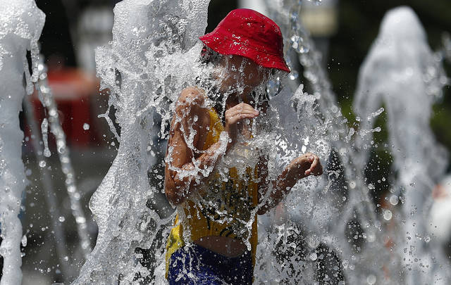 A girl cools off in a public fountain during the 2018 soccer World Cup in Krasnodar, Russia, Wednesday, July 4, 2018. (AP Photo/Manu Fernandez)