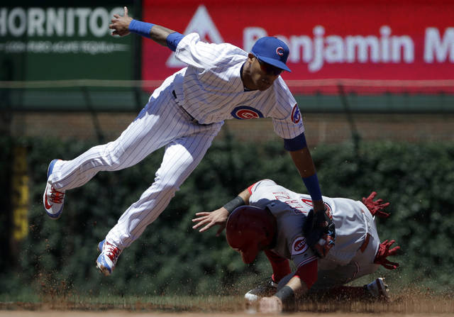 Cincinnati Reds' Jose Peraza, bottom, steals second base as Chicago Cubs shortstop Addison Russell applies a late tag during the first inning of a baseball game Friday, July 6, 2018, in Chicago. (AP Photo/Nam Y. Huh)