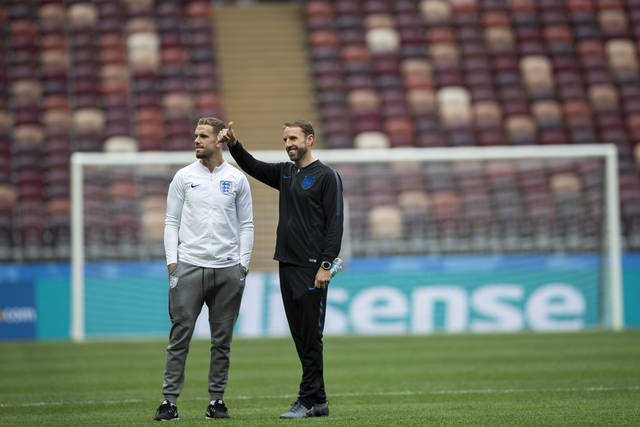 England head coach Gareth Southgate, right, gestures next to player Jordan Henderson as they walk along the pitch after England's official news conference on the eve of the semifinal match between England and Croatia at the 2018 soccer World Cup in the Luzhniki stadium in Moscow, Russia, Tuesday, July 10, 2018. (AP Photo/Francisco Seco)