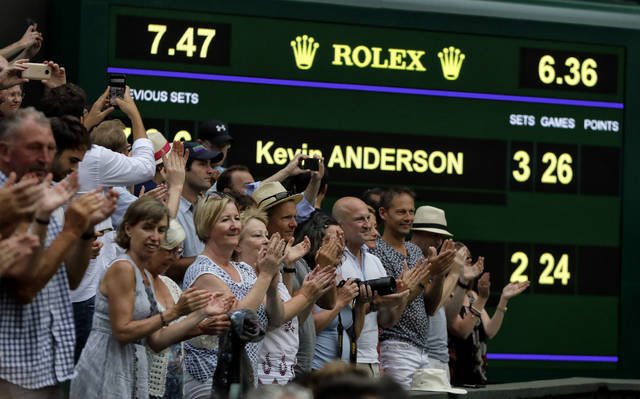 Spectators applaud as the scoreboard displays the final score in the men's singles semifinals match in which John Isner of the United States was defeated by South Africa's Kevin Anderson, at the Wimbledon Tennis Championships, in London, Friday July 13, 2018.(AP Photo/Kirsty Wigglesworth)