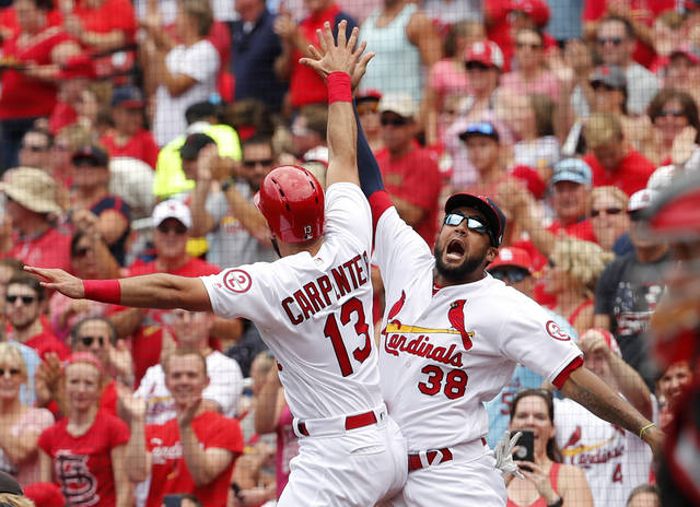 St. Louis Cardinals' Matt Carpenter (13) is congratulated by teammate Jose Martinez (38) after hitting a solo home run during the first inning of a baseball game against the Cincinnati Reds Sunday, July 15, 2018, in St. Louis. (AP Photo/Jeff Roberson)