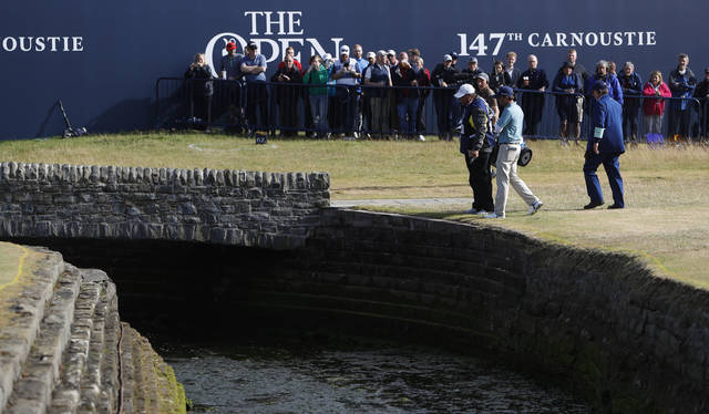 Kevin Kisner of the US talks to officials after hitting the ball into the water on the 18th hole during the second round of the British Open Golf Championship in Carnoustie, Scotland, Friday July 20, 2018. (AP Photo/Alastair Grant)