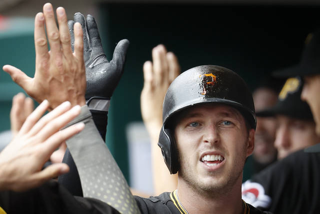 Pittsburgh Pirates' Corey Dickerson celebrates in the dugout after hitting a two-run home run off Cincinnati Reds starting pitcher Matt Harvey in the second inning of a baseball game, Sunday, July 22, 2018, in Cincinnati. (AP Photo/John Minchillo)
