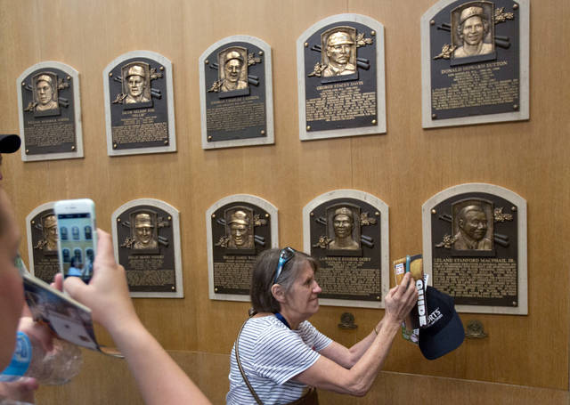 FILE - In this July 25, 2015, file photo, fans visit the Plaque Gallery at the National Baseball Hall of Fame in Cooperstown, N.Y. This weekend, brings the latest crop of inductees into the Baseball Hall of Fame, the ultimate repository of the game's yesterdays, Vladimir Guerrero, Chipper Jones, Jack Morris, Alan Trammell, Jim Thome and Trevor Hoffman. Modern players who now belong to the ages.  (AP Photo/Mike Groll, File)