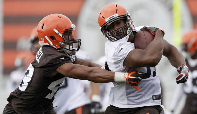 Cleveland Browns running back Nick Chubb, right, tries to avoid defensive back Elijah Campbell during NFL football training camp, Thursday, July 26, 2018, in Berea, Ohio. (AP Photo/Tony Dejak)