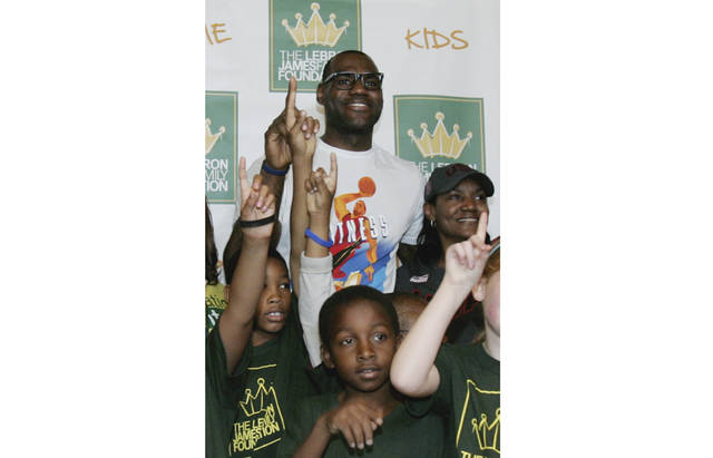"FILE - In this Aug. 19, 2012, file photo, NBA star and Akron native LeBron James and his mother Gloria James, right, pose with children participating in the LeBron James Family Foundation's Wheels for Education ""Time to Promise"" School Year event at Canal Park during an Akron Aeros game in Akron, Ohio. James, who earlier this month ended his second stay with the Cleveland Cavaliers by signing a four-year contract with the Los Angeles Lakers, has opened a public school for challenged children in his hometown. The I Promise School, which is part of the Akron Public Schools, will initially house 240 third and fourth graders. The school will expand each year, adding second and fifth grades next year and will have student from grades 1-8 by 2022. The NBA superstar will be at the school Monday, July 30, 2018,  to welcome students and make his first public comments since deciding to join the Lakers. (Karen Schiely/Akron Beacon Journal via AP, File)"