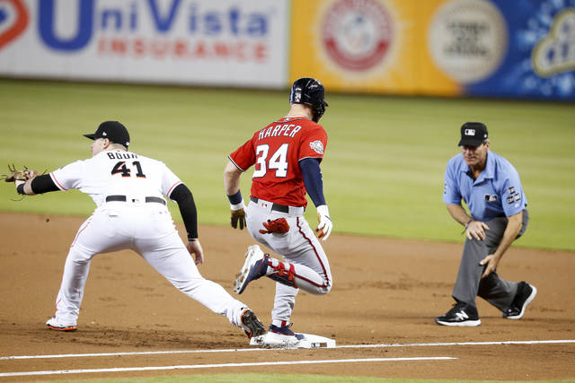 Washington Nationals' Bryce Harper, center, avoids getting put out by Miami Marlins first baseman Justin Bour, left, during the first inning of a baseball game, Sunday, July 29, 2018, in Miami. (AP Photo/Brynn Anderson)