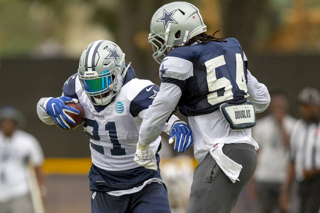 Dallas Cowboys running back Ezekiel Elliott (21) and Dallas Cowboys linebacker Jaylon Smith (54) battle on a run during NFL football training camp, Saturday, July 28, 2018, in Oxnard, Calif. (AP Photo/Gus Ruelas)