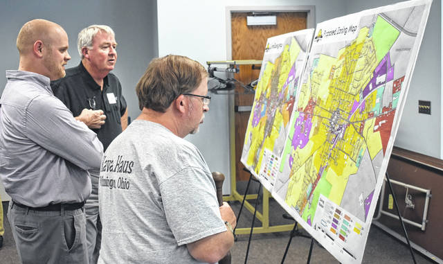 From left, Senior Planner Zach Moore of Warren County Regional Planning Commission, Wilmington Council President Mark McKay, and Bill Limbacher look at the current and proposed zoning maps at the Wilmington Zoning Update Open House on Wednesday. Moore helped the Zoning Task Force come up with the proposed map.