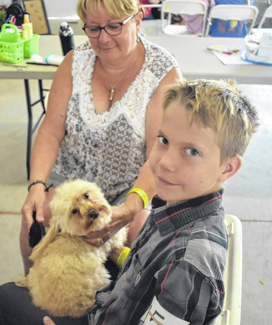 Advisor Cindy Wallace, left, and Blake Wheeler gives the pampered pooch Rocky a brushing before he goes on at the Dog Obedience, Showmanship & Skillathon at the Clinton County Fair on Thursday.