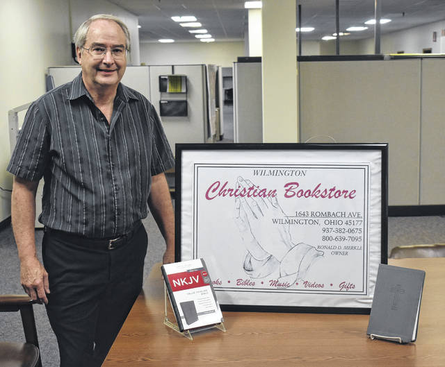 Ron Merkle, owner of the Christian Bookstore in Wilmington, stands next to a display featuring two of the 1,000 Bibles purchased by a customer for Merkle to give out.