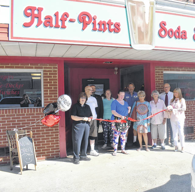 Breya Hodge, center, cuts the ribbon to her new restaurant, Blanchester Downtown Diner and Gifts, surrounded by locals and officials on Tuesday.