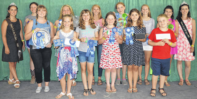 The first-place winners and state fair qualifiers in the cooking classes at the Family & Consumer Sciences (FCS) and General Awards Program are, from left in the front row, Anna Garnai (holding a platter), Addison Swope, Danica Henderson, Patience Persing, Autumn Smith and Owen Koch; and from left in the back row are FCS Queen Carrie Robinson, Jenna Hanlon, Makayla Henry, Katie Hughes, Carolyn Koch, Allie Houseman, Paige Bryant and Clinton County Junior Fair Queen Falesa Fyffe.