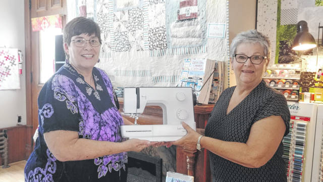 Nancy Stanforth, right, won a Bernette Sew N Go machine that was given away as a prize in connection with the 10th anniversary of the Cotton Junky Quilt Shop. Presenting the prize is Carol Earhart, left, co-owner of the Cotton Junky Quilt Shop.
