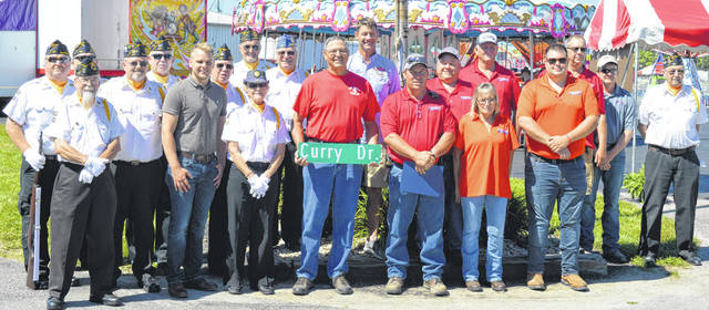 The Senior Fair Board, American Legion members and others assembled for a photo after the annual flag-raising ceremony to officially open the Clinton County Fair near the front gate on Main Street.