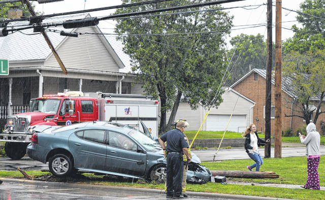 A utility pole split after an accident Tuesday morning, July 31 at Main and Hale Streets in Wilmington. Two vehicles were heading eastbound on Main Street when the vehicle in the right-hand lane made a turn toward Hale Street, striking the vehicle in the left lane and forcing it into the intersection and into a utility pole, said police. The driver of the vehicle that struck the pole was transported to Clinton Memorial Hospital by life squad, and is reported to have received minor injuries. The woman running in the photo is relieved to see the woman holding a phone at the far right standing and OK, with a hug to follow.