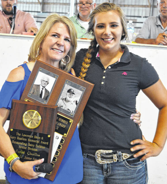Sarah Quallen, right, earned the Lawrence Dean and Gary Quallen Memorial Award for being the outstanding dairy exhibitor in the senior division. She is with presenter Jennifer Cohen, left, at the Clinton County Junior Fair livestock sales.
