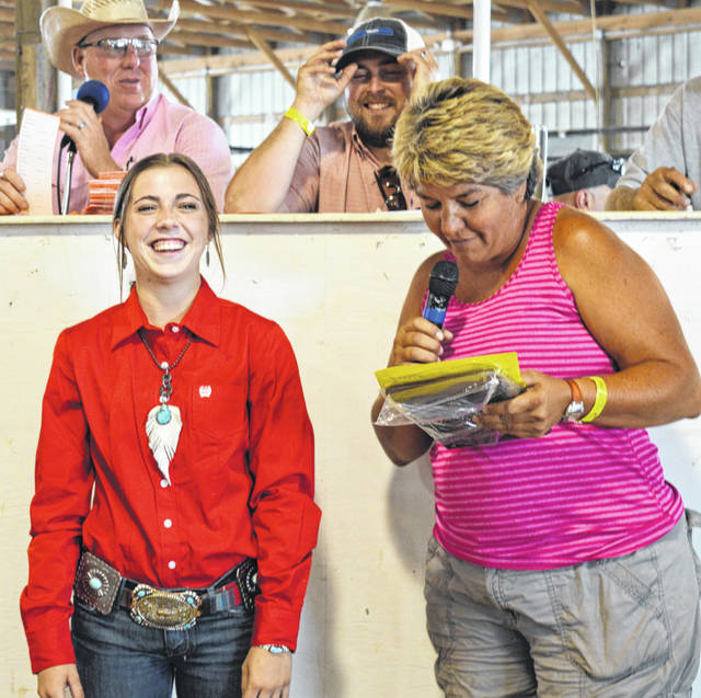 "Gracee Stewart, left foreground, is presented the award for ""Outstanding Market Hog Project, Senior"" by Sherri Kile, right foreground, during the 2018 Clinton County Junior Fair Swine Sale."