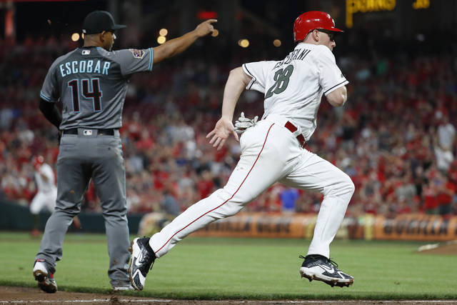 Cincinnati Reds' Anthony DeSclafani (28) runs home to score on a bunt single by Billy Hamilton off Arizona Diamondbacks starting pitcher Clay Buchholz and a throwing error by Buchholz during the seventh inning of a baseball game, Friday, Aug. 10, 2018, in Cincinnati. (AP Photo/John Minchillo)