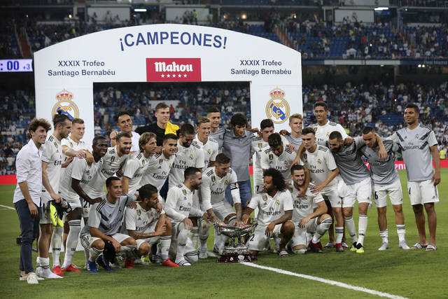 FILE - In this Saturday, Aug. 11, 2018 file photo, Real Madrid players pose with the trophy after winning the Santiago Bernabeu trophy soccer match between Real Madrid and AC Milan at the Santiago Bernabeu stadium, in Madrid. Real Madrid's rebuilding process after the departures of Cristiano Ronaldo and Zinedine Zidane gets its first test against crosstown rival Atletico Madrid in the UEFA Super Cup in Estonia on Wednesday, Aug. 15, 2018. (AP Photo/Andrea Comas, File)